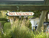 No Vacancy. Sign hanging from sign in garden Royalty Free Stock Photo
