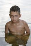No verão do menino encaracolado-de cabelo sério é banhado no rive Imagem de Stock Royalty Free
