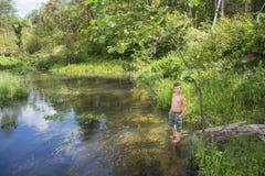 No verão há um menino no banco de rio Foto de Stock Royalty Free