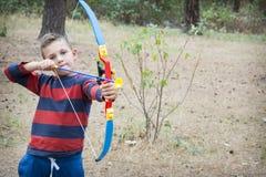 No verão na floresta o menino dispara em uma seta imagens de stock