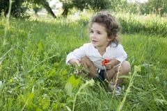 No verão, na menina encaracolado que estão na grama alta, e na grama Imagens de Stock Royalty Free