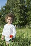 No verão, na menina encaracolado que estão na grama alta, e na grama Imagem de Stock Royalty Free