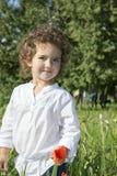 No verão, na menina encaracolado que estão na grama alta, e na grama Fotografia de Stock Royalty Free