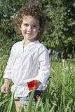 No verão, na menina encaracolado que estão na grama alta, e na grama Imagens de Stock