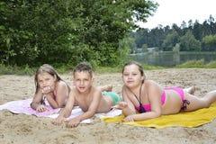No verão, na praia perto do rio são as crianças na areia Fotografia de Stock Royalty Free