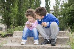 No verão que senta fora a menina e o menino encaracolado-de cabelo pequenos a Foto de Stock Royalty Free