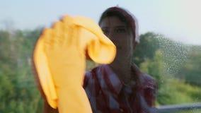 No vidro de janela é refletido, mulher de sorriso nas luvas, limpando a janela por produtos de limpeza da pulverização, usando-se video estoque