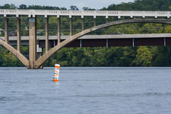 No wake idle speed buoy. Buoy sits in the water warning boaters to slow down. Bridge in background Stock Images