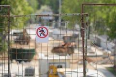 No walking pedestrian warning sign on the metalic gird.  Royalty Free Stock Photography
