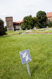 No Walking sign on Lawn in Wawel Castle. Forbidden grass featuring a No Walking sign and tourists in the background. Located at Wawel Castle in Cracow, Poland royalty free stock images