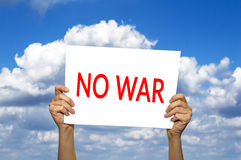 NO WAR card in hand against blue sky with clouds. Royalty Free Stock Photography