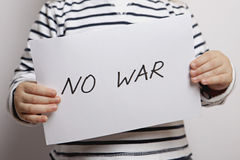 NO WAR Children For Peace. No war text written on paper held by a child stock images