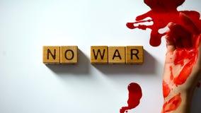 No war phrase made of wooden cubes, bleeding hand on table, political conflict. Stock photo stock photos