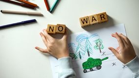 No war text on cubes, child painting military situation, political problems. Stock photo royalty free stock photos