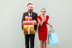 No way! Amazed bearded man in red hat and woman in red dress, ho Stock Photo