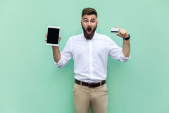 No way! Online shopping. Businessman holding hands credit card and tablet and looking at with shocked face. royalty free stock images