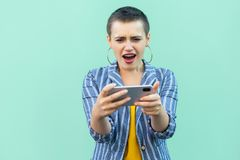 No way! Portrait of beautiful unbelievable with short hair young woman in striped suit standing, playing game on her phone with royalty free stock images