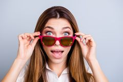 No way! Really?! Shocked attractive girl in sunglasses is holding them with her fingers. She is amazed and with wide open mouth an. D eyes on pure light Royalty Free Stock Photos