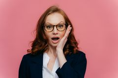 Really no way? Shocked red haired woman touches cheek, opens mouth widely, looks surprisingly at camera, finds out shocking news,. Wears spectacles, elegant royalty free stock images