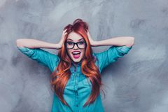No way! Really?! Shocked red head foxy pretty girl in glasses an. D casual clothes is holding her head with hands. Ginger is excited and with open mouth and Stock Photo