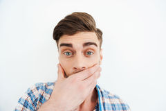 No way!. Shocked young man covering mouth with hand and looking at camera while standing against white background Royalty Free Stock Photo