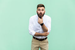 No way! Young adult with beard with shocked facial expression, holdings hands on chin. Indoor, studio shot Stock Images