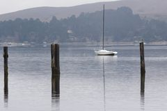 No Wind. A sailboat sits on a quiet bay Royalty Free Stock Photo