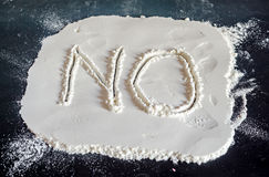 NO word write in white powder, black background, no drugs, close Royalty Free Stock Photo