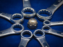 Nob Nut. Circle of spanners surrounding a nut Stock Photography