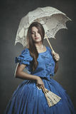 Noble beautiful woman posing with umbrella and fan. Venice carnival Royalty Free Stock Photo