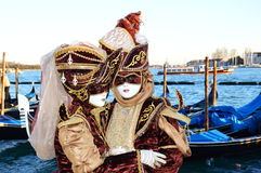 Noble couple in wine-red costumes. Noble couple wearing masks and an outfit in wine-red and gold, medieval style Royalty Free Stock Photo