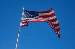 Noble flag of United States of America waving on the wind on cl. Ear sky background stock photography