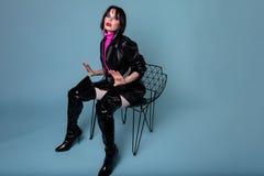 Noble Frau der Mode, die im Studio darstellt kniehohe Lederstiefel sitzt lizenzfreies stockbild