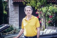 Noble 40 Jahre alte Sportler, die auf Cabrioletautotür sitzen Lizenzfreie Stockfotografie