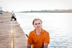 Noble 40 Jahre alte Sportler, die auf dem Pier sitzen Lizenzfreie Stockfotografie