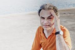 Noble 40 Jahre alte Sportler, die seinen Kopf halten Stockfotografie