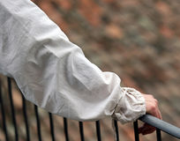 Noble's hand with the ancient dress resting on the railing of th Royalty Free Stock Image