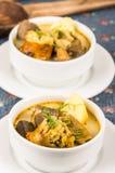 Noble Umhüllung der Kartoffelsuppe mit Fleisch und vegatables, gedient in den weißen Schüsseln, die auf Tabelle, blaue Tischdecke stockfotos
