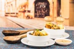 Noble Umhüllung der Kartoffelsuppe mit Fleisch und vegatables, gedient in den weißen Schüsseln, die auf Tabelle, blaue Tischdecke stockbild