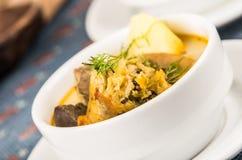 Noble Umhüllung der Kartoffelsuppe mit Fleisch und vegatables, gedient in den weißen Schüsseln, die auf Tabelle, blaue Tischdecke lizenzfreie stockfotos