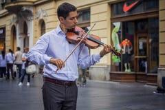 Nobler junger Violinist, der auf einer Straße spielt Stockbilder