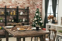 Nobody empty dining room with Christmas meal. On wood table Christmas tree on the background Royalty Free Stock Image