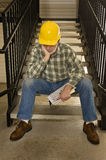 Nobody Is Hiring Worker Laid Off. Vertical shot of construction worker out of work sitting on stairs Royalty Free Stock Photo
