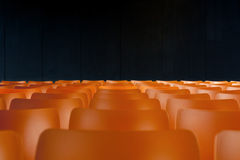 Nobody is listening. Rows of empty orange seats Royalty Free Stock Images