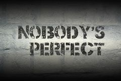 Nobody`s perfect gr. Nobody`s perfect stencil print on the grunge white brick wall Stock Images