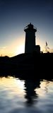 Nobska Silhouette. Nobska lighthouse silhouetted by sun and reflected in water Royalty Free Stock Photo