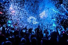 Noc klubu sylwetki tłumu ręki up przy confetti kontrpary sceną Zdjęcie Royalty Free