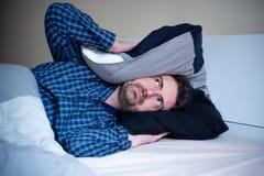 Noc mężczyzny i hałasu cierpienia bezsenność w łóżku zdjęcia royalty free