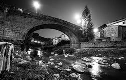 Noc pejzaż miejski zaświeca na rzece pod rzymskim mostem Fotografia Stock