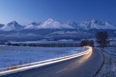 Noc samochody zaświecają na górach na horyzoncie i drodze obraz royalty free
